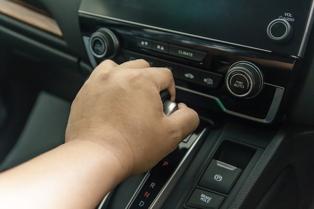 Hand on automatic gear shift, man hand shifting an automatic car, luxury car design interi
