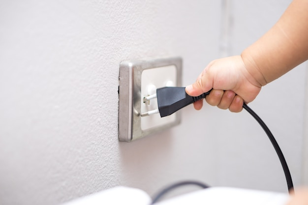 Hand of a baby trying to insert plug into electrical outlet covered with safety plugs