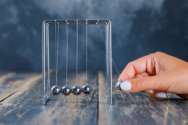 Hand balancing ball on newton's cradle