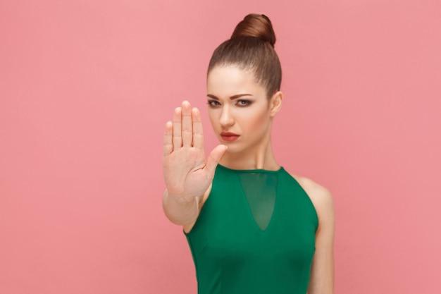 손 금지, 안돼! 손을 보여주는 여자, 정지 신호. 표현 감정과 감정 개념입니다. 스튜디오 촬영, 분홍색 배경에 고립