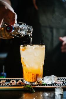 Рука бармена делает коктейль. коктейль имеет листья апельсина и мяты.