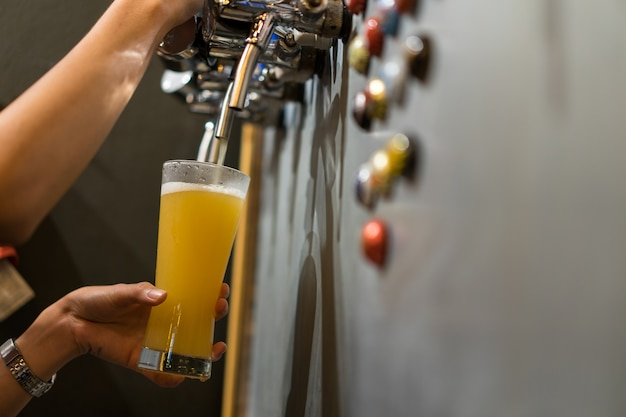 Hand of bartendy pouring a craft beer in tap.