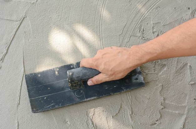 Hand on be bound with cement , do cement work, apply cement (over a surface)