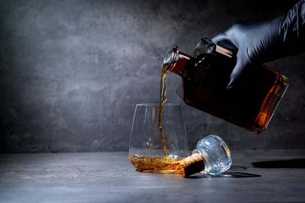 Hand in a black glove pours whiskey from a square bottle into a glass on a dark gray cement surface
