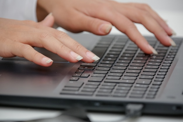 Hand on the black keyboard of a computer typing text