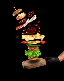 Hand in black latex glove hold an empty vintage brown wooden cutting board.  cheeseburger ingredients fall on the board: sesame bun, fried egg, tomato, cheese, ketchup and meat cutlet