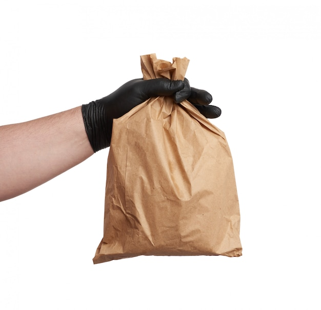 Hand in a black latex glove holds a full paper bag of brown craft paper