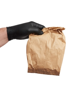 Hand in a black latex glove holds a full paper bag of brown craft paper,