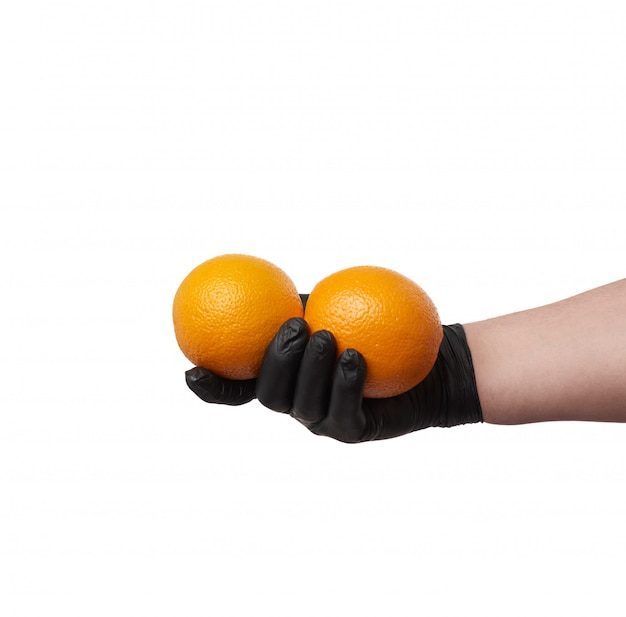 Hand in a black latex glove holds two round ripe oranges, part o