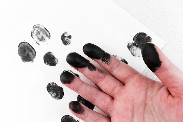 Hand in black paint and fingerprints