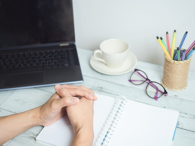 Hand on blank paper notebook with laptop and coffee and glasses on the desk workspace concept