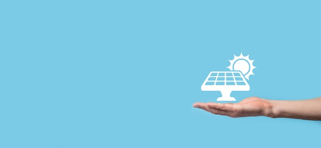 Hand on a blue background holds the icon symbol of solar panels. renewable energy, solar panels station concept, green electricity