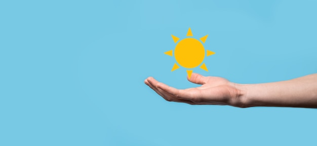 Hand on blue background holds sun icon symbol.sustainable source of electricity,power supply concept