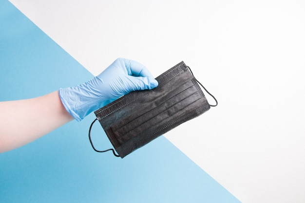 Hand in a blue disposable medical glove holds a black face mask, white with blue background