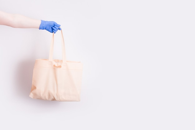 A hand in a blue disposable medical rubber glove holds a shopping bag for shopping