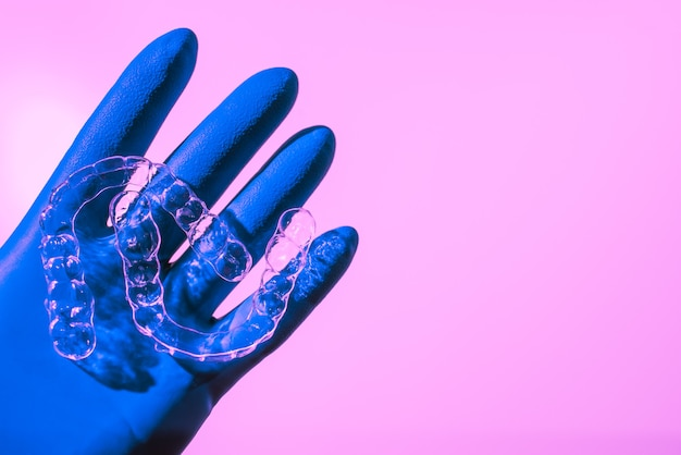 A hand in a blue glove holds aligners for aligning teeth on a pink background. plastic braces dentistry retainers to straighten teeth.