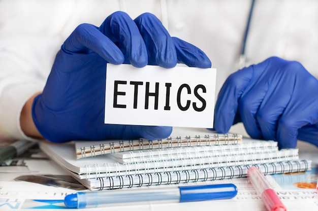 Hand in blue glove with white card. doctor holding a white paper card with text: ethics. healthcare conceptual for hospital, clinic and medical busines. concept word ethics.