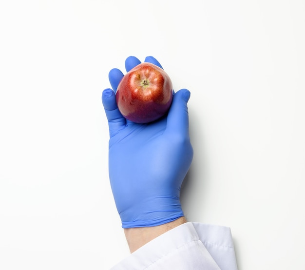 Hand in a blue latex glove holds a ripe red apple on a white background, healthy food concept, top view