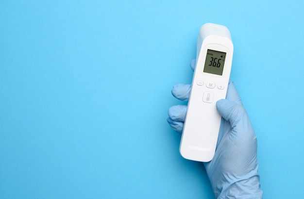 Hand in blue latex gloves hold an electronic thermometer to measure temperature, non-contact device, display shows temperature 36.6 degrees