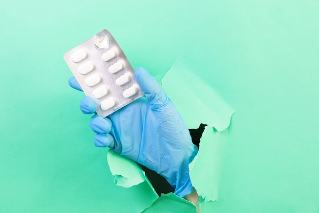 Hand in a blue medical glove with a pack of pills. through a hole in green paper.  medicine, pharmacy, health. minimalism, .