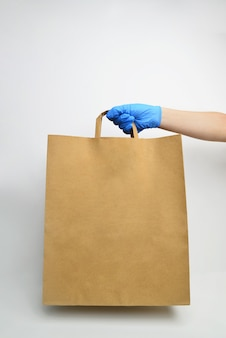 Hand in blue medical gloves holds craft paper bag on white