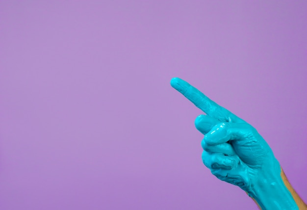 Hand in blue paint on a purple background, finger points to copy space