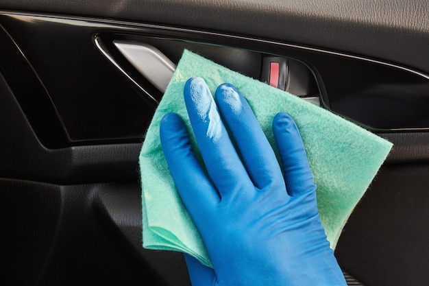 Hand in blue protective glove is wiping with a cloth an interior handle of car door