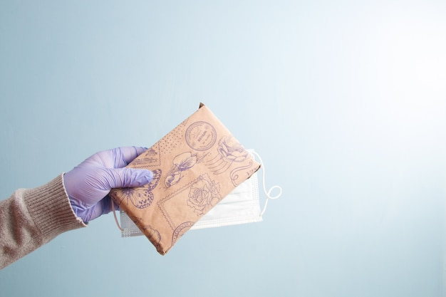 A hand in a blue rubber disposable glove holds a protective face mask and a gift wrapped in kraft wrapping paper
