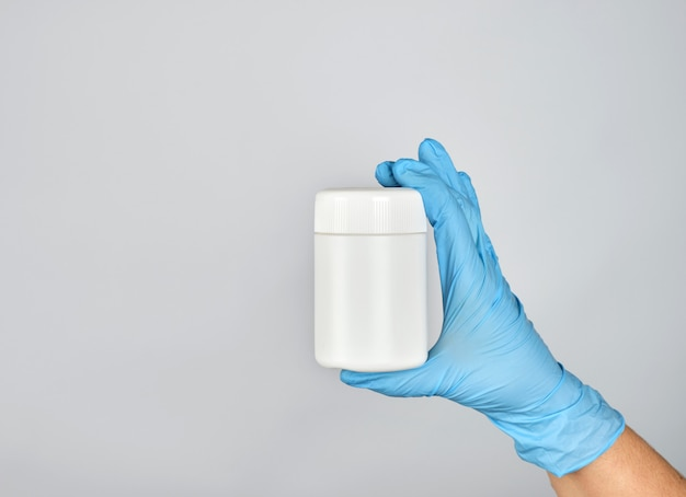 Hand in blue sterile glove holds white plastic jar with pills