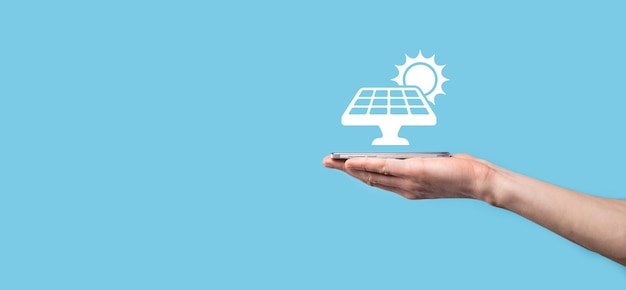 Hand on a blue surface holds the icon symbol of solar panels