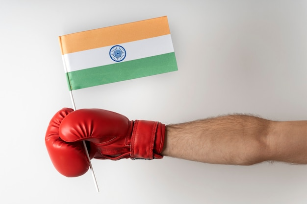 Hand in boxing glove holds the flag of india. white background.