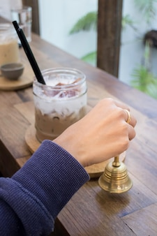 Hand on brass bell in coffee shop