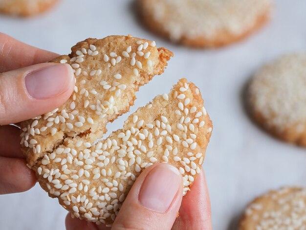 Рука ломает свежее вкусное кунжутное печенье. закройте вверх.