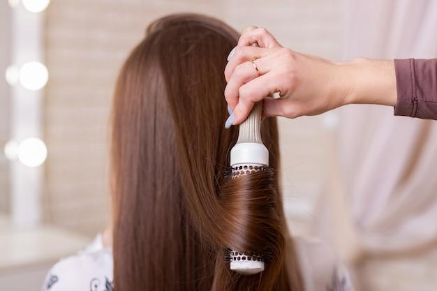 Hand brushing long brunette hair in beauty salon