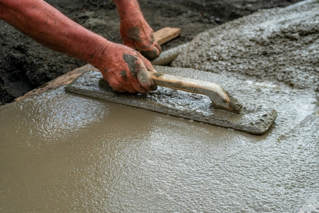 Hand builder with trowel leveling concrete