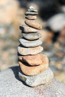 ビーチで滑らかな石の山を手で構築します。高品質の写真
