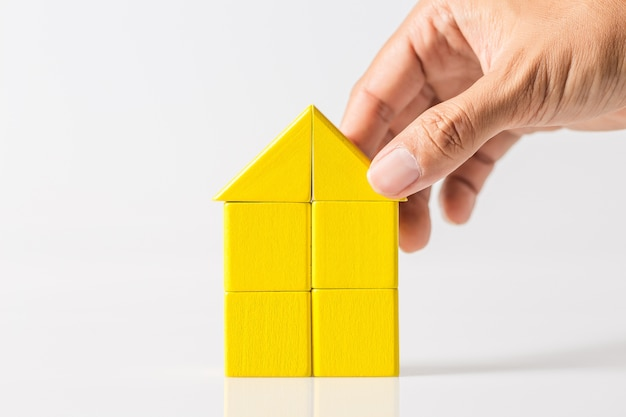 Hand building house (real estate) with wooden blocks