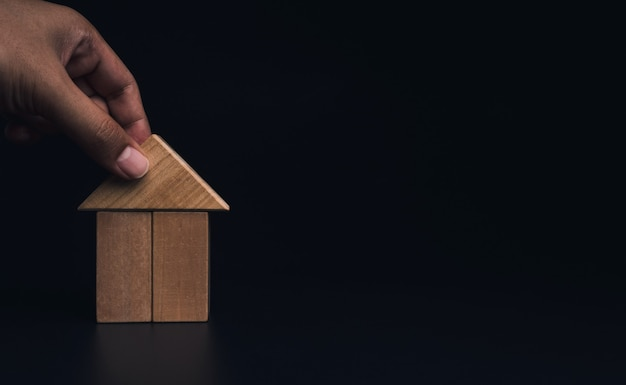 Hand building house with wooden blocks, laying of the roof on dark background with copy space. property planning. house building construction symbol, eco style, loan concepts.