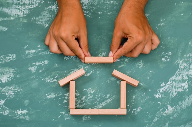 Hand building house with wooden blocks.