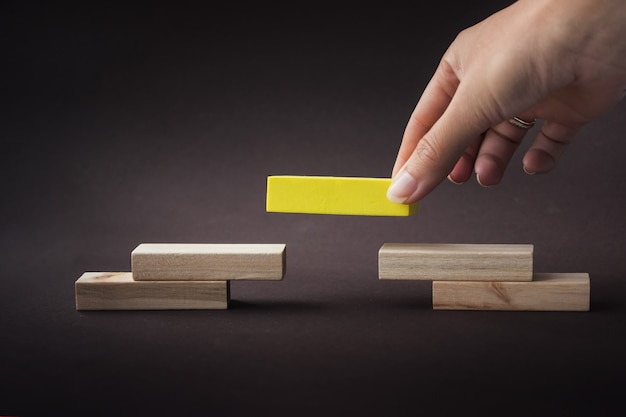 Hand building pyramid with empty wooden blocks, symbolizing career ladder. leader concept.