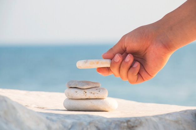 Hand building a stone tower on the beach.