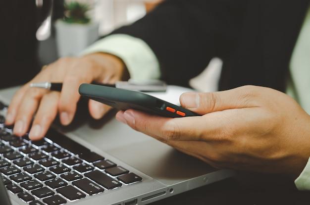 Рука деловой человек, держащий мобильный телефон и набрав на клавиатуре компьютера.