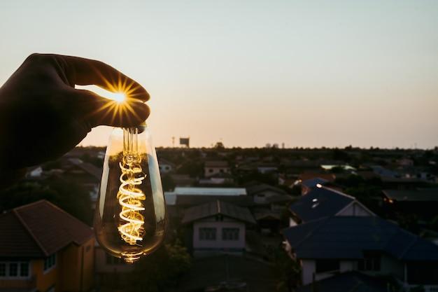 電球を持っている手のビジネスマン。代替エネルギー、アイデア、節電の革新とインスピレーションの概念。
