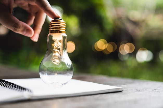 노트북에 전구를 들고 손 비즈니스 남자. 대체 에너지, 아이디어, 절약 전기 혁신 및 영감 개념.