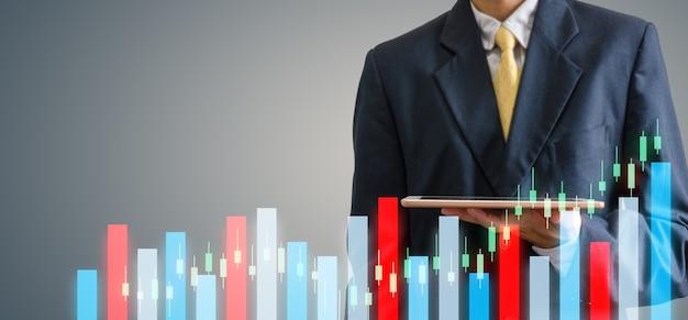 タブレットを持っている手ビジネスマン。証券取引所市場グラフの概念