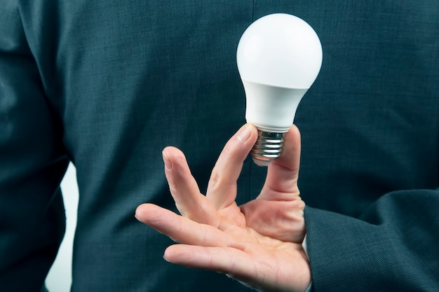 Hand of a business man holds an led lamp
