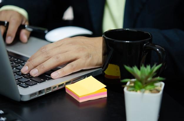 Рука деловой человек печатает на клавиатуре компьютера.