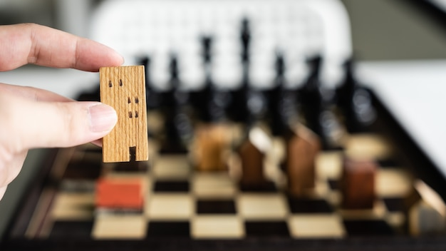 Hand of business man moving building and house models in chess game