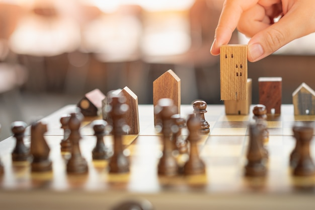 Hand of business man moving chess to building and house models in chess game.