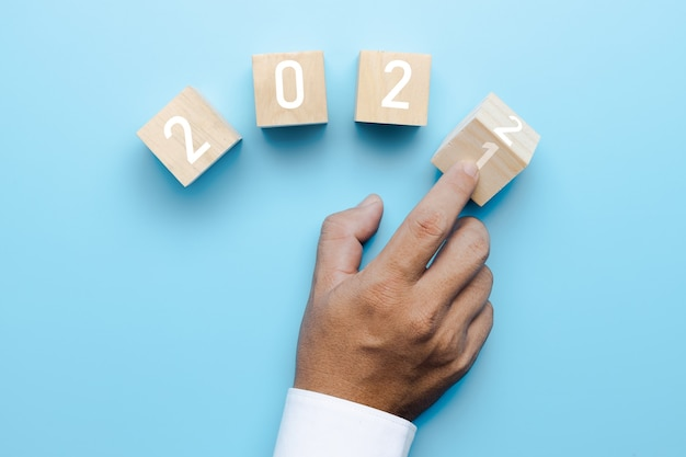 Hand of business people turn 2021 to 2022 on cube box